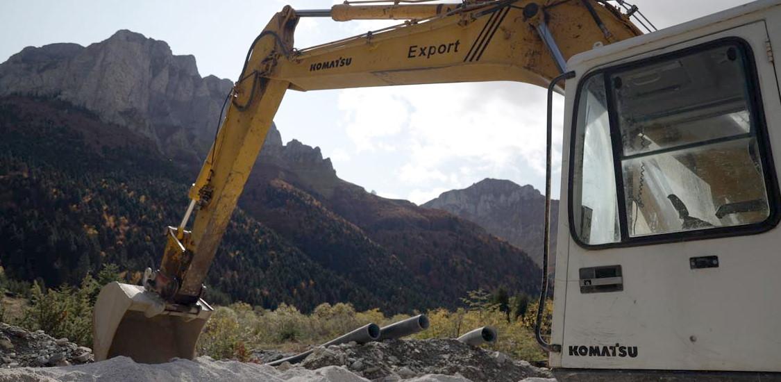Фотографија на која се гледа багер, цевки и планина